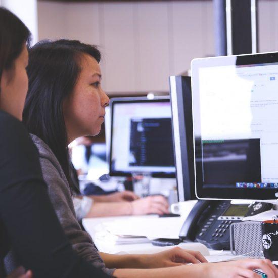 Woman Helping a Woman Navigate a Computer UI