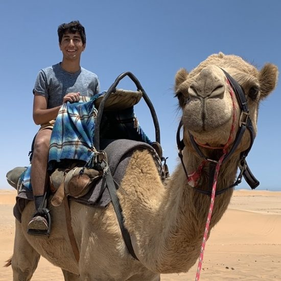 Student studying abroad and riding a camel