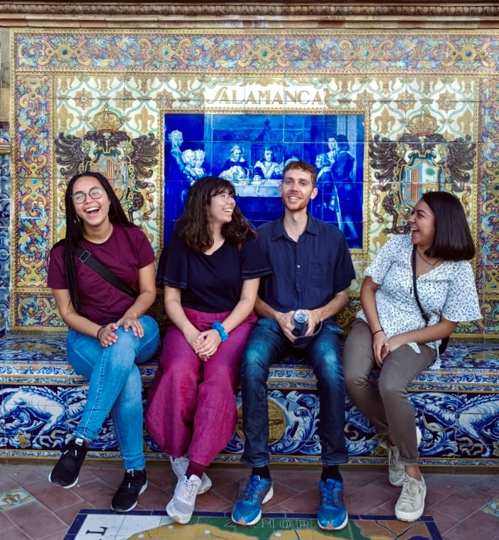 UIC students sit on a step in front of a colorful mural in Salamanca.