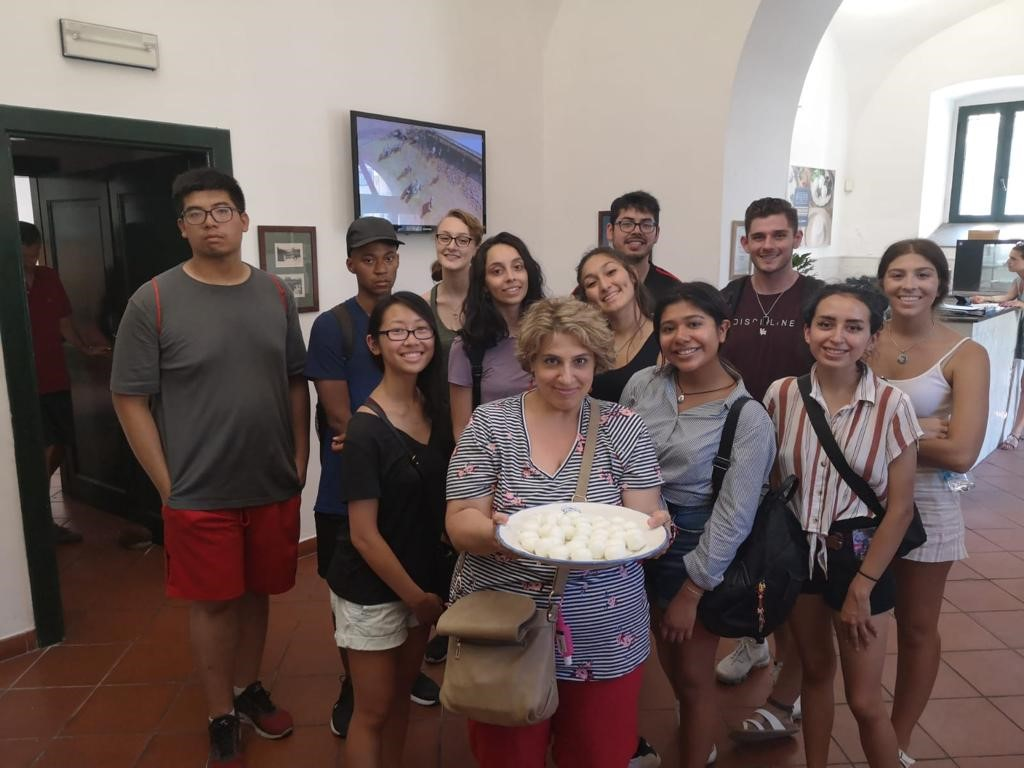 UIC students on the Italian Language and Culture in Salerno program with faculty member Maria Iusco. Maria is holding a plate of Italian food.